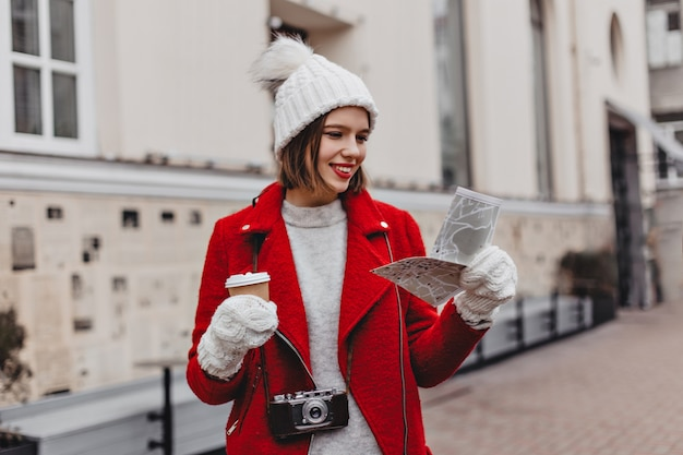 Beautiful tourist in white hat and red coat holding map, exploring city. portrait of girl in mittens on background of building.