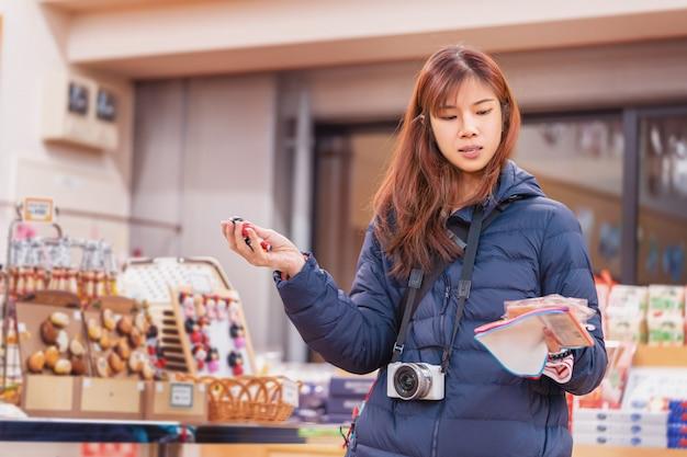 Красивый турист с фотоаппаратом делает покупки в сувенирном магазине