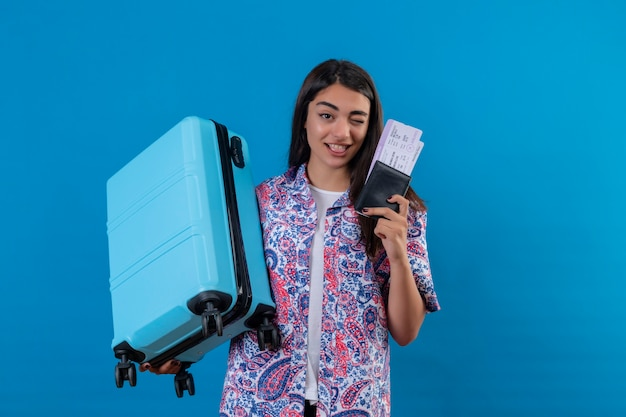 Красивая туристическая женщина, держащая туристический чемодан и паспорт с билетами с улыбкой на лице, подмигивая счастливой и позитивной концепцией путешествия, стоящей над синим пространством