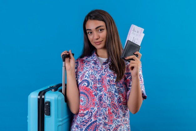 Beautiful tourist woman holding travel suitcase and passport with tickets  with smile on face happy and positive travel concept standing over blue space
