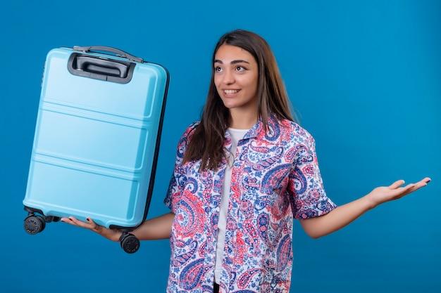 Bella donna turistica che tiene la valigia di viaggio diffondendo le sue mani ai lati sorridendo allegramente in piedi sopra lo spazio blu isolato