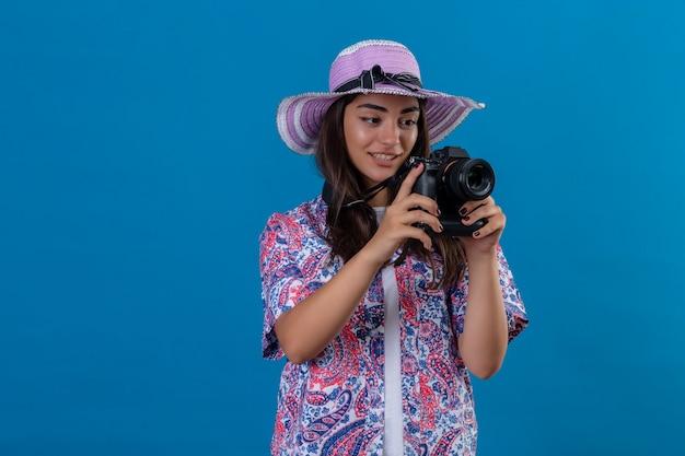 孤立した青い空間に顔の肯定的で幸せな立っている笑顔で写真カメラで夏帽子の美しい観光女性