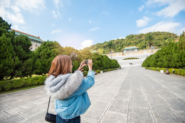 Beautiful tourist woman is photographing  in a famous place taipei, taiwan