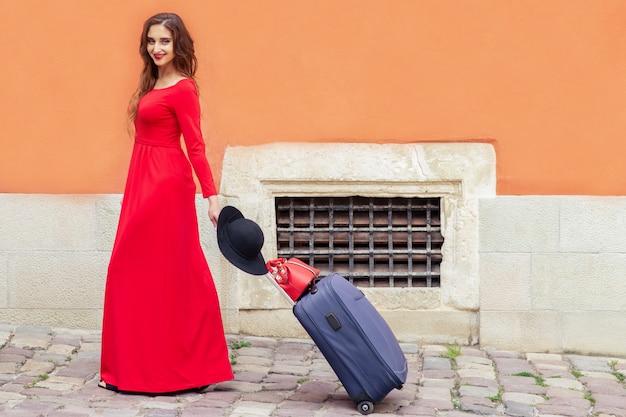 Красивая туристическая женщина тянет чемодан на дороге улицы города.
