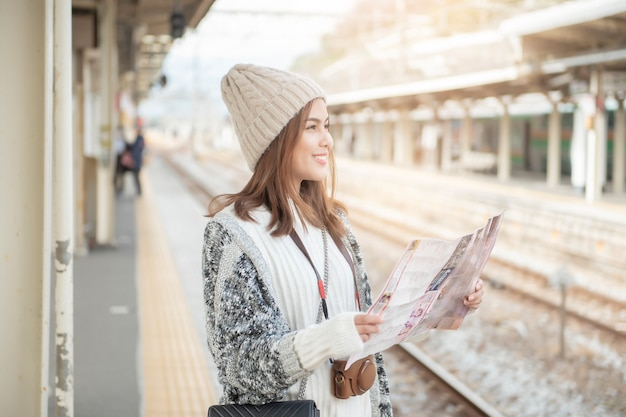Beautiful tourist  woman is standing on railway platform  with her map