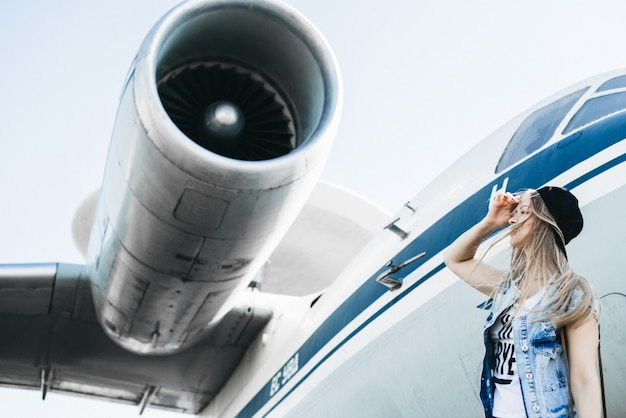 Beautiful tourist woman posing near the plane against jet engine holding hand on forehead looking into distance waiting for something or someone