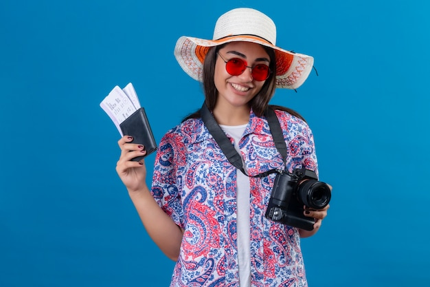 Beautiful tourist woman in summer hat wearing red sunglasses standing with photo camera holding passport and tickets smiling cheerfully ready to holiday over isolated blue space