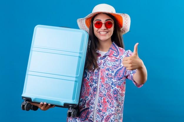 Bella donna turistica in cappello estivo che indossa occhiali da sole rossi in piedi con la valigia di viaggio che sorride allegramente mostrando i pollici in su sopra lo spazio blu isolato