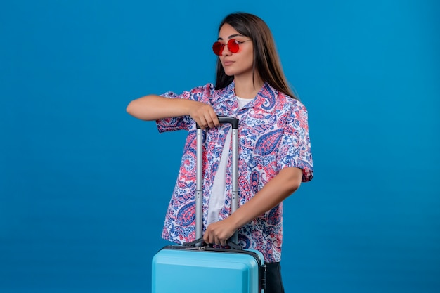 Beautiful tourist woman wearing red sunglasses holding travel suitcase looking confident ready to travel standing over isolated blue space