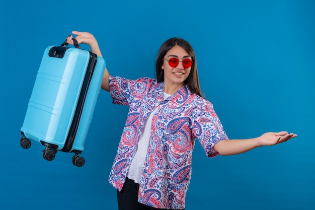 孤立した青い空間を歓迎するジェスチャーで腕を組んでフレンドリーな立っている笑顔の旅行スーツケースを持って赤いサングラスをかけている美しい観光女性