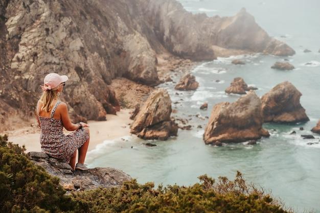 아침 햇살에 인상적인 praia da ursa beach를 즐기는 아름다운 관광 여성. 신트라, 포르투갈의 초현실적 인 풍경. 대서양 해안선 풍경.
