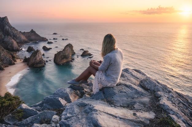 Красивые туристические женщины, наслаждаясь закатом на пляже прайя-да-урса.