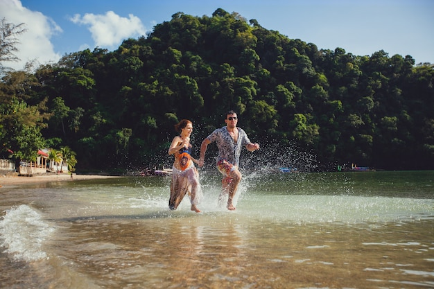 Beautiful tourist young couple holding hands together running along the beach shore with mountains and blue sea water and sky, outdoors, create splashes. lifestyle travel and tourism, honeymoon