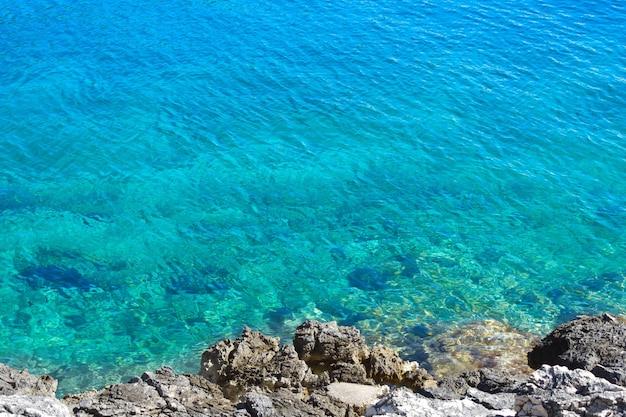 Красивое, прозрачное бирюзовое адриатическое море, остров хорватия, крупный план. каменистый берег