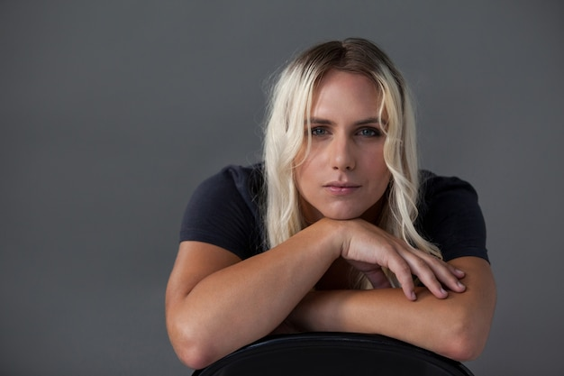 Beautiful transgender woman leaning on chair over gray wall