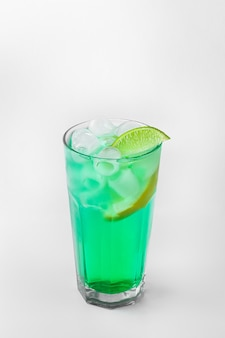 Beautiful transparent glass of summer drink. green lemonade with ice and lime isolated on a white background with natural shadows