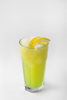 Beautiful transparent glass of summer drink. green and yellow lemonade with ice and lemon isolated on a white background with natural shadows