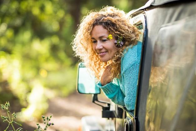 Красивая концепция путешествия взрослая женщина наслаждается лесом, садится в машину и за окном