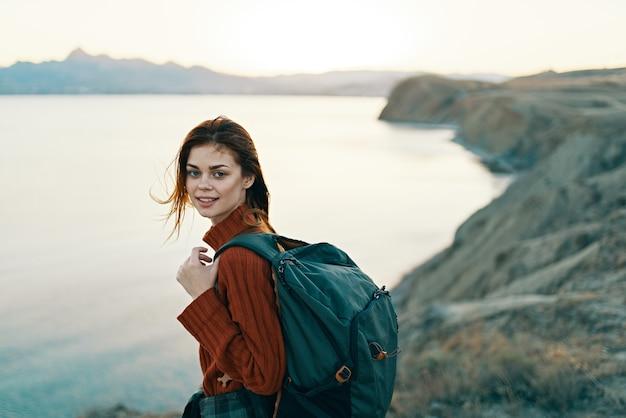 自然と高い山の海の空に山のバックパックを持つ美しい旅行者