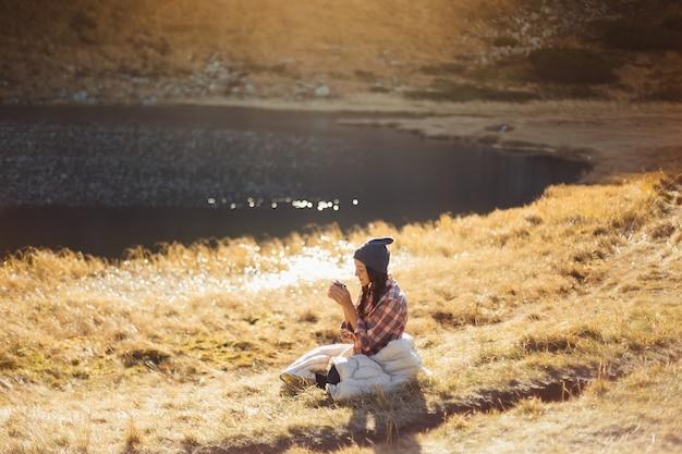湖のキャンプ旅行の近くで飲み物を飲みながら山でハイキングする美しい旅行者の女性