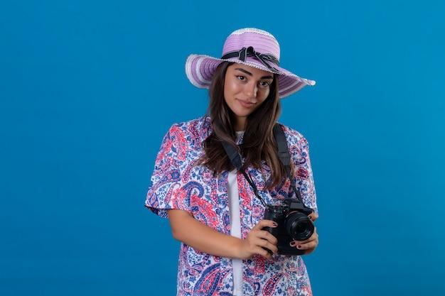 孤立した青い空間に顔の肯定的で幸せな立っている笑顔で写真カメラで夏帽子の美しい旅行者女性