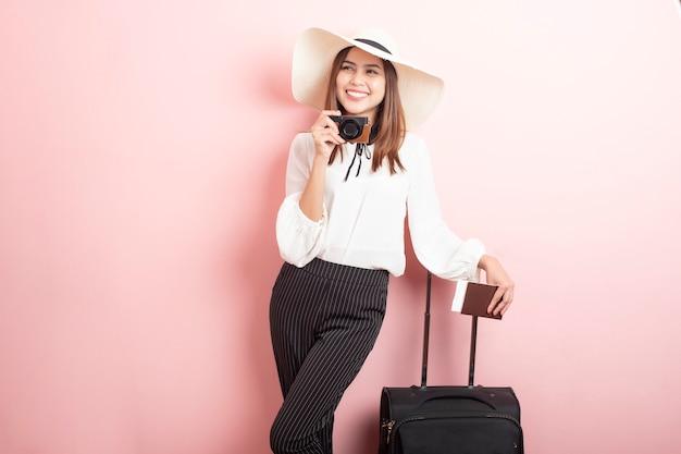 美しい旅行者の女性はピンクの背景でエキサイティングです
