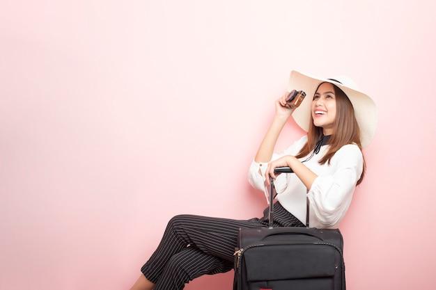 美しい旅行者の女性はピンクの壁でエキサイティングです