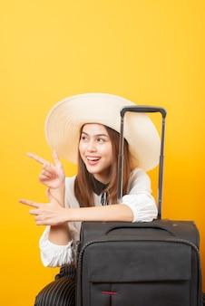 美しい旅行者の女性は黄色の背景にエキサイティングです