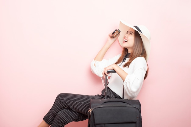 Beautiful traveler woman is exciting in pink background