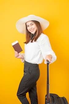Beautiful traveler woman is exciting on yellow  background