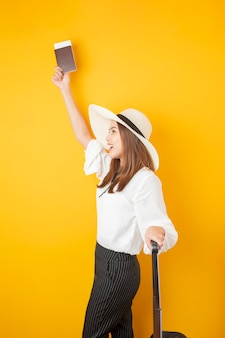 Beautiful traveler woman is exciting on yellow  wall