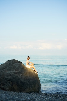 Beautiful traveler young woman sitting on stone coast with backpack and enjoying view of sea summer