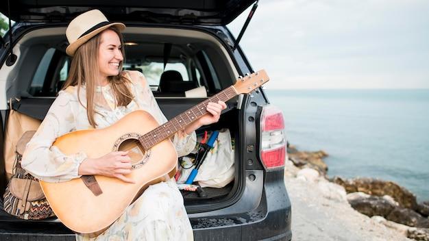 Красивый путешественник играет на гитаре в отпуске
