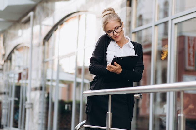 Beautiful trendy blond business woman in glasses talking by mobile phone and standing outside a office building.