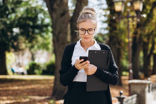 Красивая модная блондинка деловая женщина в очках с смартфон и папка документов в ее руках на открытом воздухе.
