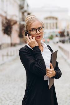 Красивая модная блондинка деловая женщина в очках с смартфон и сумочка документов в ее руках на открытом воздухе.