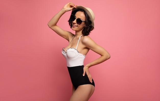 ピンクの表面に隔離された日光で休息を楽しんでいる間、水着、帽子、サングラスの美しいトレンディなフィットの女性