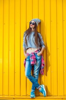 黄色の壁に美しいトレンディな十代の少女