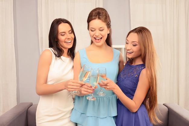 Красивые модные молодые девушки держат бокалы с вином
