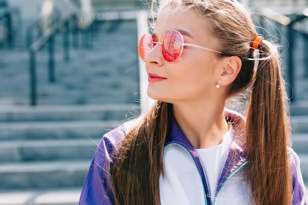 ピンクのサングラスと笑顔のスタイリッシュな服を着た美しいトレンディな若い女性