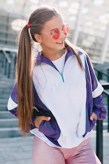 Bella giovane donna alla moda in vestiti alla moda che posano con il sorriso