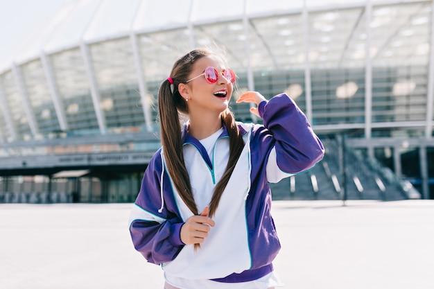 Bella giovane donna alla moda in vestiti alla moda indossando occhiali da sole rosa e ridendo