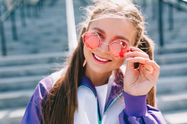 Bella giovane donna alla moda in vestiti alla moda indossando occhiali da sole rosa e sorridente