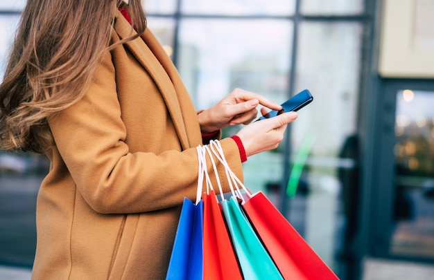 Beautiful trendy young woman with many colorful shopping bags in good mood with smart phone and credit card while walking in the mall during black friday