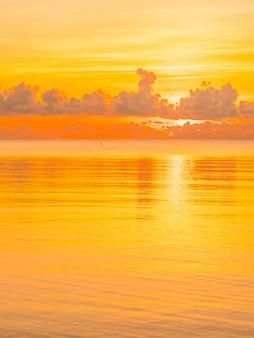 日の出や日没時に雲と空を持つ美しい熱帯のビーチと海の海の風景