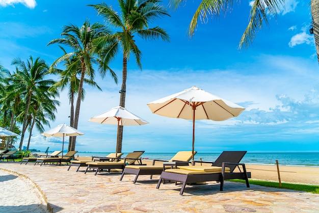 旅行や休暇のためのホテルリゾートのプールの周りの傘と椅子と美しい熱帯のビーチと海