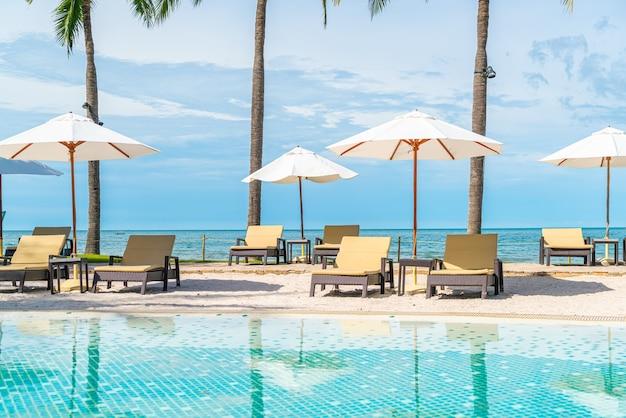 여행 및 휴가를위한 호텔 리조트의 수영장 주변에 우산과 의자가있는 아름다운 열대 해변과 바다