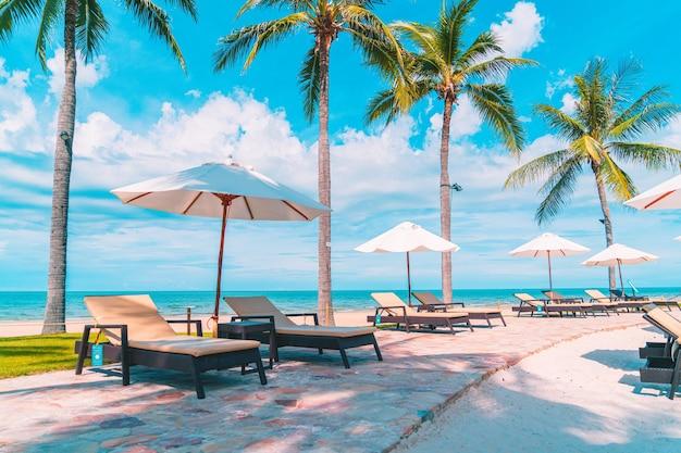 여행 및 휴가를위한 호텔 리조트 수영장 주변의 우산과 의자가있는 아름다운 열대 해변과 바다