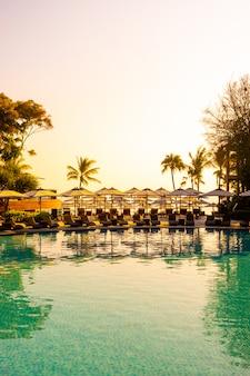 旅行や休暇のためのホテルリゾートのスイミングプールの周りの傘と椅子のある美しい熱帯のビーチと海