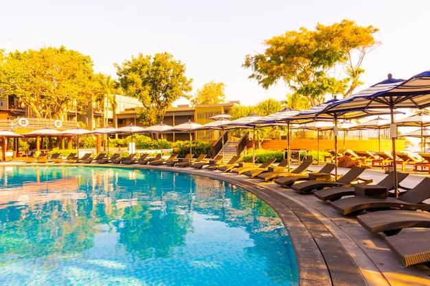 ホテルリゾートのスイミングプールの周りの傘と椅子のある美しい熱帯のビーチと海